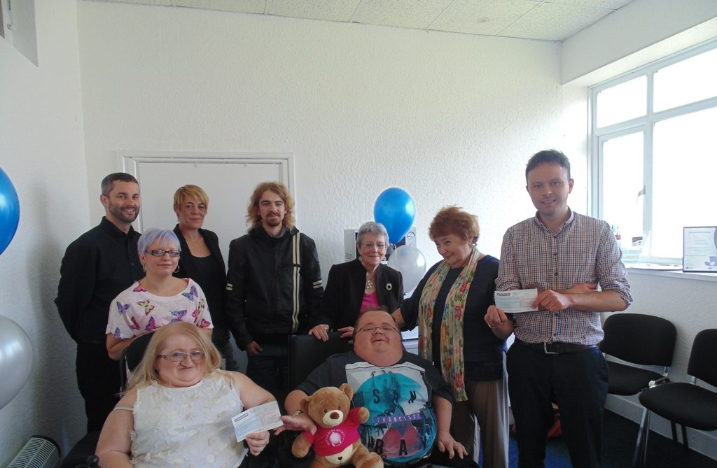 Accessible News volunteers presenting cheques to representatives from the British Lung Foundation and the Brittle Bone Society